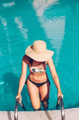Young woman in large hat exiting her pool